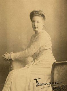 """Princesa Tatiana Constantinovna. Ela está sentada em uma cadeira virada em parte para a esquerda e está descansando as duas mãos sobre o braço direito da cadeira. Ela está usando um vestido longo de cor clara. A fotografia é assinada e datada no canto inferior direito: """"Tatiana 1909"""""""