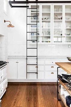 white kitchen with rolling ladder for easy access to tall cabinets