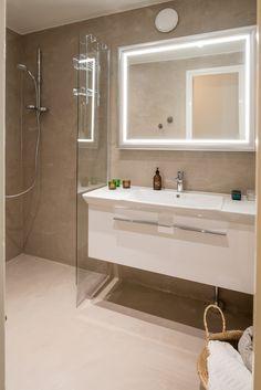 Kylpyhuone sai uuden ilmeen mikrosementillä, valkoisella pesuallaskaapilla ja isolla kehystetyllä valopeilillä.