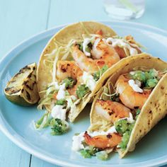 Grilled Shrimp tacos  1/2 cup sour cream 3 tablespoons mayonnaise 3 tablespoons milk 1/2 teaspoon ground cumin 1 1/2 pounds large shrimp, peeled 3 tablespoons butter, melted 2 large garlic cloves, minced 4 limes, cut into quarters 1/2 teaspoon kosher salt 8 6-inch corn tortillas 2 to 3 cups finely shredded green cabbage Bottled green tomatillo salsa