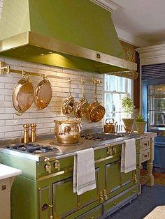 Green Retro-Style Range and Hood with Copper Accents and French Top. Copper cookware and backsplash bar accentuates the look.