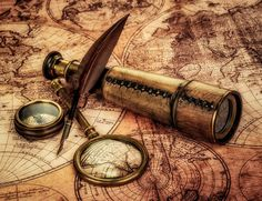 Vintage magnifying glass, compass, goose quill pen and spyglass lying on an old map.»