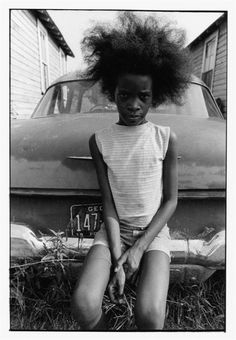 Girl with Afro sitting on bumper of old car, Georgia, 1970 Paul Kwilecki. This isn't an Afro I've ever seen! Just sayin. American Women, My Black Is Beautiful, Beautiful People, Afro Girl, African Diaspora, We Are The World, Documentary Photography, Black People, Black And White Photography