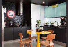 O Studio RO+CA apostou em objetos decorativos cheios de cor para este ambiente de móveis e revestimentos escuros. Enquanto o armário suspenso assume um azul pastel, a mesa e um letreiro ornamental abraçam o amarelo vibrante. Na parede de pastilhas negras, placas de trânsito adicionam um pouco de vermelho.