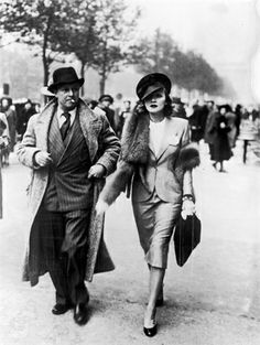 Film star Marlene Dietrich (1901 – 1992) and her husband Rudolf Sieber (Rudy Sieber) (1897 – 1976) walking in Paris. She is wearing a tailored suit designed by Travis Banton with a fox fur and a peak hat tilted over one eye. Her husband sports a fleck tweed overcoat over a chalk stripe suit. (Photo by Keystone/Getty Images)