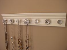 jewelry holder This wall necklace organizer has 7 decorative cabinet knobs featuring large rhinestone center on off white background 20* by Gotahangup on Etsy https://www.etsy.com/listing/112033322/jewelry-holder-this-wall-necklace