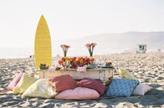 Beach picnic or formal event, this tablescape is pure joy. Surrounded by mismatched, oversized pillows in beautiful fabrics, the table sits low to the ground, with a surfboard nearby and pretty floral centerpieces and feminine china on the table.