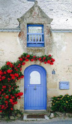 Nesta porta, o azul dialoga com a cor da janela e contrasta com as tonalidades das flores. Em Guérande, na França.