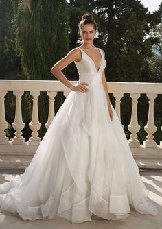 You'll be ready for the aisle in this classic deep V-neckline clean ball gown. The satin bodice with an organza ruffle skirt will light up your day.