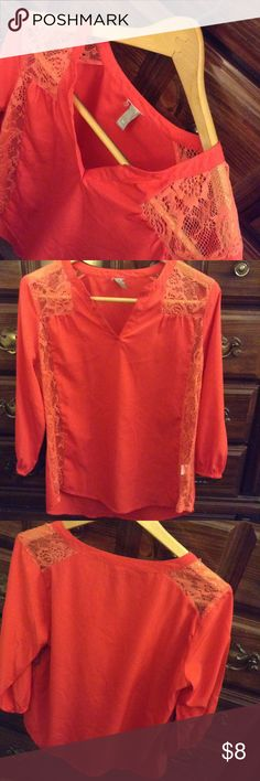 Reddish/orange colored top with lace detail Not sure of the brand on this one but super cute and comfortable! Says size medium but may be a lil oversized. Lace detail at the shoulders and down the sides of the front. V-neck in style and comes from a smoke free home. There was a small flaw in the lace but this has been mended. Consult the fourth pic for this but it's not noticeable. Bust measures 21 inches laid flat. Hips are 23. Length is 27.5. This top is 3/4 sleeve and have elastic cuffs…