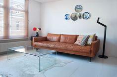 cognackleurige bank van leer, houten witte vloer en kunst aan de muur.  www.ijzersterkinterieurontwerp.nl
