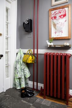 Homepolish Interior Design | A deep red detailed paint job for the radiator and pipe offset the moody gray walls.