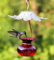 Perry's Hummer Hut - Red Glass Hummingbird Feeder features a brass leaf-designed roof to shield the nectar from sun and rain. The roof is stamped in brass with a leaf design. The feeder is made from red glass with one flower feeder port. A beautifully designed copper hanger holds the glass feeder in place.