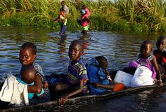 Children cross a body of water on a canoe to reach a registration area prior to a food distribution carried out by the United Nations World Food Programme (WFP) in Thonyor, Leer state, South Sudan, Saturday.Siegfried Modola/Reuters
