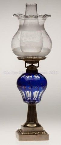 """CUT OVERLAY PUNTY AND OVAL STAND LAMP, cobalt blue cut to colorless pyriform font with worn gilt decoration, brass stem, double-step marble base with stamped brass ornamentation, No. 2 fine line collar. Fitted with a period set-up comprising a Novelty lip burner, shade ring, cut and frosted Oregon shade, and lip chimney. Boston & Sandwich Glass Co. Third quarter 19th century. 18 3/4"""" H to top of shade, 10 1/2"""" H to top of collar, 4 1/2"""" SQ base. Shade 6 1&#x..."""
