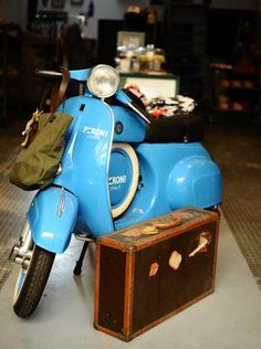vintage 90cc Vespa scooter being used in storefront for a dash of color.