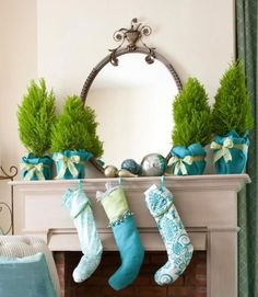 Wrap containers of cypress trees with blue felt or burlap and secure with ribbon. Click to see more Christmas mantel ideas. | blue and silver Christmas decorations