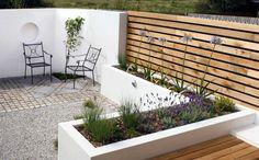 moderne terrassengestaltung weiße wand kieselsteine pflanzen