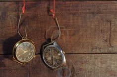 two-old-watches-hanging-on-fish-hooks-on-wooden-background