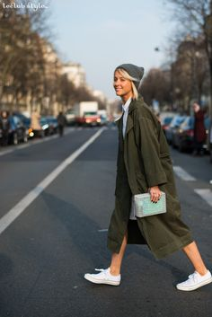 Womenswear Street Style by Ángel Robles. Fashion Photography from Paris Fashion Week. Woman smiling on the street, she wears khaki duster coat, Converse sneakers and grey beanie, after Issey Miyake show, Paris.