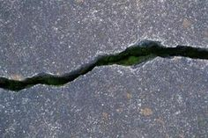 Garage floor cracks happen no matter how carefully the concrete gets poured. Different factors cause cracks to appear. A common cause of heaved concrete is from temperature. Cement Driveway, Driveway Repair, Cement Patio, Concrete Driveways, Concrete Slab, Concrete Filler, Walkways, Painting Concrete Porch, Concrete Floor Leveling