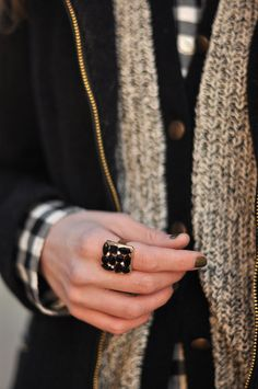 Black and white plait shirt with thick oatmeal cardigan, and black zip up jacket, big ring small black stones, and dark nail polish.