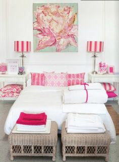 Pretty bedroom in white and bright pinks.  The white bed is decorated with light and dark pink pillows in different patterns.  Bright pink striped lampshades complement the array of throw pillows on the bed and stacked on the side table shelves.  The large rose painting over the bed ties everything together.