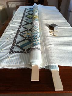Basting a quilt without kneeling: quilt top rolled on one board, quilt backing rolled on another board, batting floats in between the two boards.Basting without kneeling. Very well explained! Excellent link credit, too.Quilt Basting Breaking You Down? Colchas Quilting, Quilting Frames, Quilting Tools, Free Motion Quilting, Quilting Tutorials, Machine Quilting, Quilting Projects, Sewing Projects, Beginner Quilting