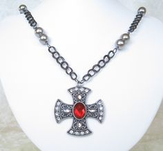 """Austere and beautiful, this necklace and earring set conveys the look and feel of medieval times: religion was part of daily life, and noble women carried its symbols proudly. Lustrous, pewter colored glass pearls stud the black double link chain, while an extra large cross, decorated with clear and ruby red rhinestones, is the focal point. 20"""" long, the cross adds 2"""". Matched earrings: 1 1/2"""" in length. I've treated the metals with my own process to prevent tarnishing. $40"""