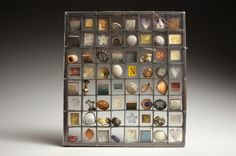 Brooch - copper and perspex square frame with 64 compartments containing slate, shells, printed tin, buttons, pressed petals, branded wood, printed paper, stones and other found objects