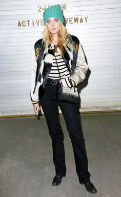 Elsa Hosk pairs a teal beenie, with a two-tone bomber jacket, a striped sweater, black pants, and black heeled oxford shoes