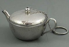 An antique hammered sterling silver tea ball in the shape of a teapot.