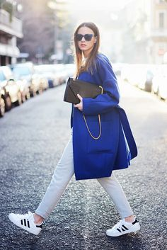 striped Sneakers tie in with the colour of the pants, reducing contrast and giving a sporty look to the bright bold clean-structured coat.  Polished hair/ clutch/ sunglasses help to move this look up a notch