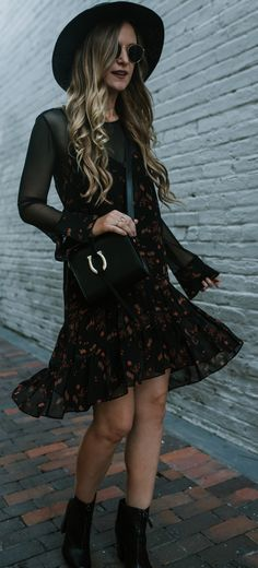 Edgy spring transition outfit with black floral dress, sheer sleeves, and zip up ankle booties #edgyoutfit #bohooutfit #blackbooties #blackcrossbody