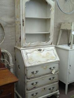 SOLD - This antique drop front secretary has a hutch top with a single door ( no glass). It has been painted creamy white antique and heavily distressed. Original metal hardware is complete and matching. 3 drawers for storage and the drop front desk offers additional cubbies and small drawers. This cabinet measurements 27 inches across the front , 16 inches deep and it stands approximately 76 inches tall. This Unique Piece can be seen in booth H9 at Main Street Antique Mall 726...