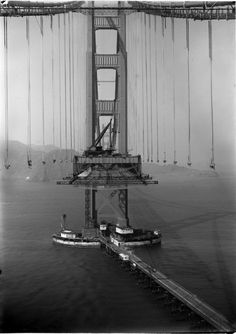 San Francisco. Golden Gate Bridge with suspension cables and not enough road yet.