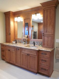 This custom master bathroom vanity with its bump out design, offers a unique and dynamic look. There is a variety of storage options including appliance garages, pull out grooming station between sinks and plenty of drawer space. The six inch back splash provides visual interest and highlights the quartz counter top. Warm cherry cabinets promote an inviting and warm feel to this wonderful master bath.