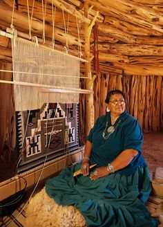 weaving in a hogan ... notice how the loom fits with the overhead beams