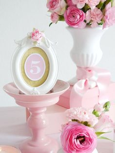 For your DIY wedding centerpiece, gather the following materials: spray paint matching your table colors, ceramic candleholders, small oval photo frames, printable table numbers, vintage saucers, gold crepe paper, scissors, hot glue, foamy double-sided tape and paper rosebud embellishments.