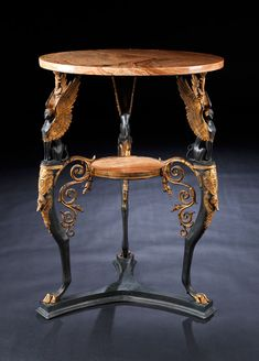 Gueridon First half of the 19th century. In the form of a Roman antique table. Frame in cast iron, gold plated. Three-legged, legs connected by a Y-shaped bottom rib with profiles, with paw feet. Back to top slim pulling up with winged sphinxes wide, where the superscripts wings carry the round, brown veined marble top. Held between the legs of volutes round intermediate plate in marble, kept with gold plated trim.