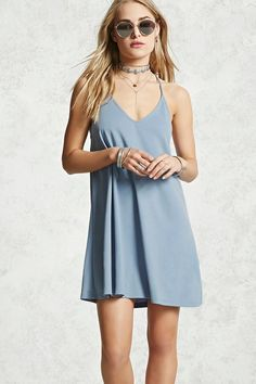 A soft knit dress featuring a plunging v-neckline, cami straps, and ruching detail at the back neckline.
