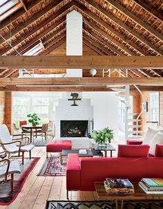 Modern rustic living room with exposed beams and red white and black decor.