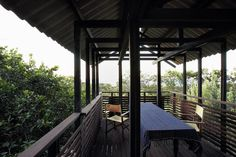This is a photograph of a table and chairs sitting on the timber decking of the belvedere of the Mooloomba House. It has timber balustrades and a corrugated roof.
