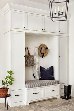 White cabinets accented with oil rubbed bronze hardware frame a white built-in mudroom bench topped with a gray cushion placed beneath polished nickel hooks lit by a Darlana Lantern.