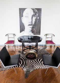 The simple pink chair cushions make a big impact in this glossy black-and-white room.   - ELLEDecor.com