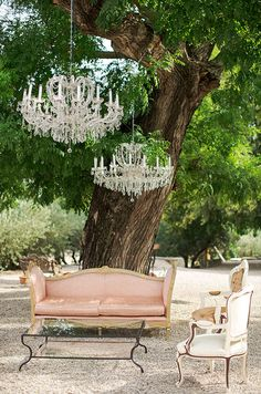 An outdoor lounge area goes sophisticated with the addition of crystal chandeliers hanging from tree branches.