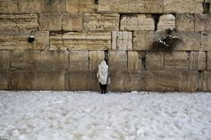 An Ultra-Orthodox Jew prays at the snow-covered compound of the Western Wall in the Old City of Jerusalem.