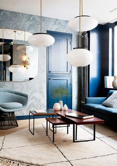 Living space with a large area rug, a blue sofa, and layered pendant lights