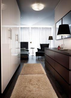 Mustanruskea PAX-vaatekaappi, jossa valkoiset korkeakiiltoiset FARDAL-ovet sekä mustanruskea MALM-lipasto