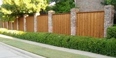 This beautiful wood fence is attached two brick columns.